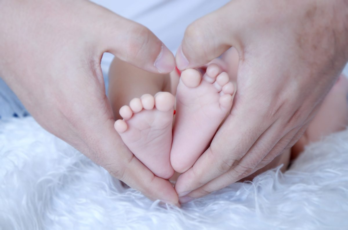 手と赤ちゃんの足
